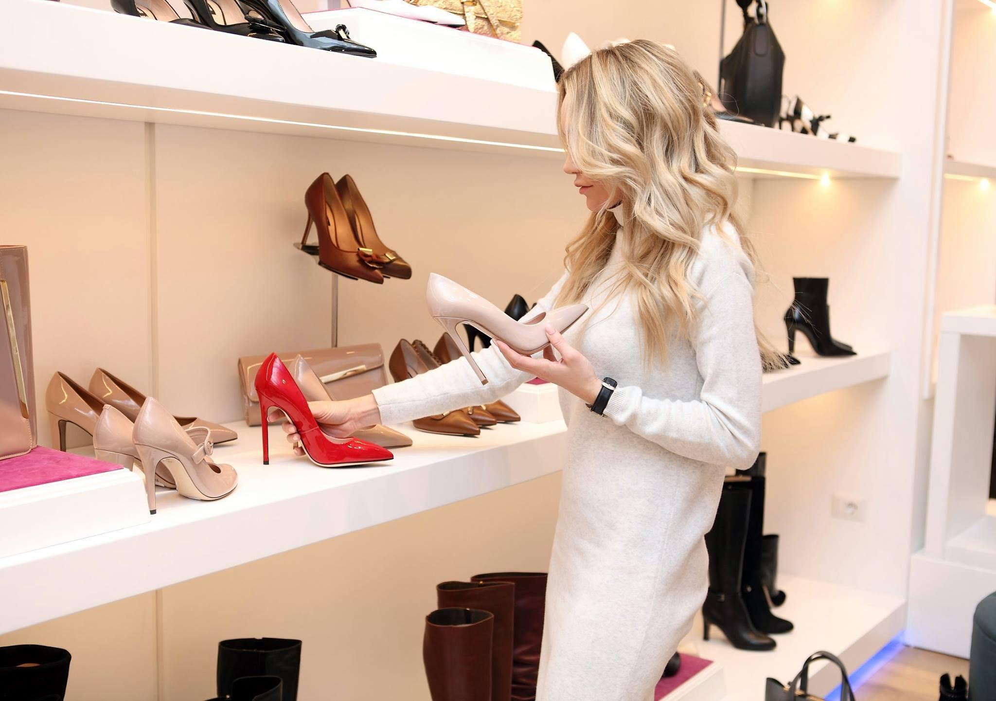 Kobieta wybierająca szpilki z półki sklepowej